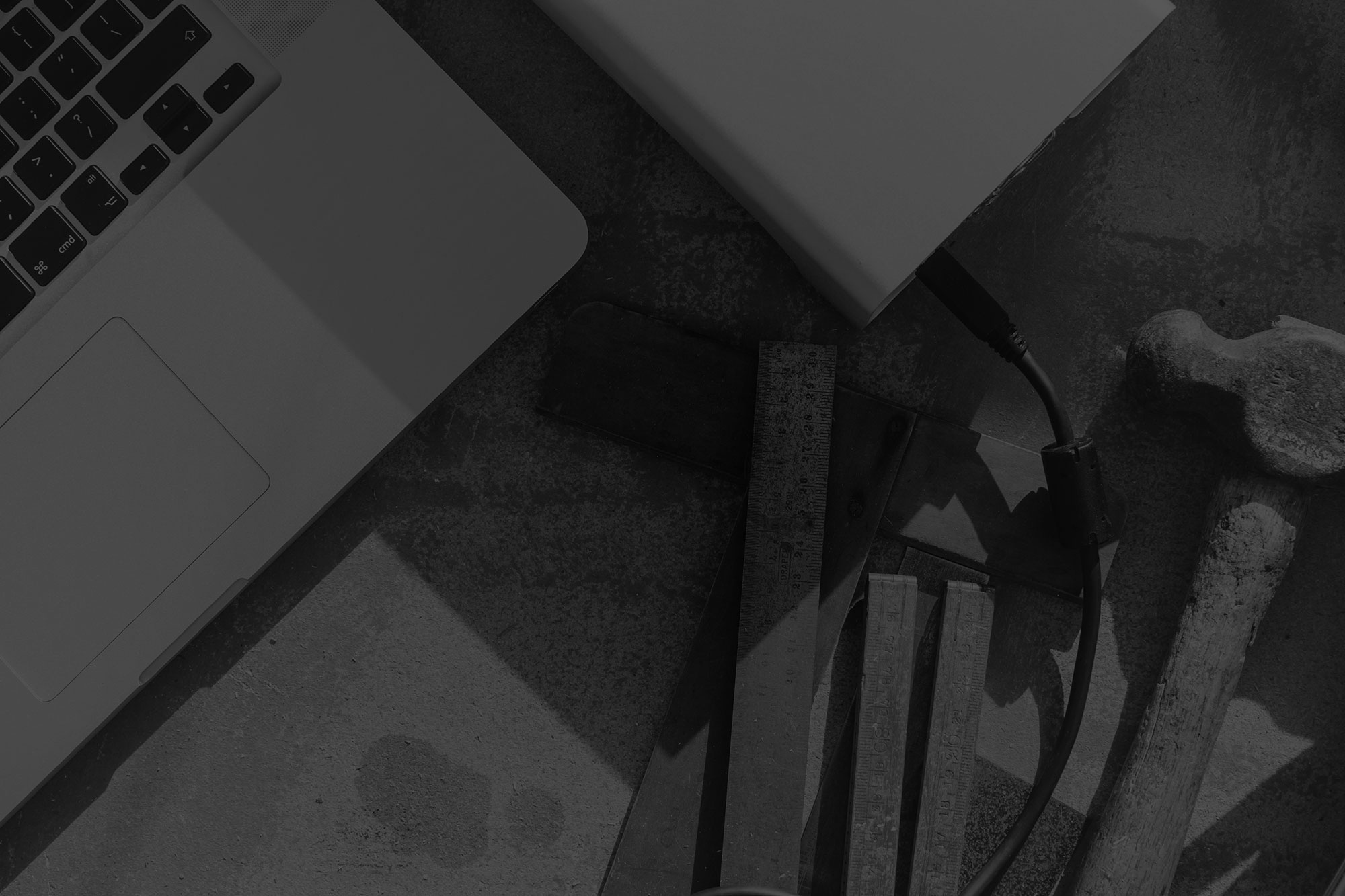 Close up of black and white image of laptop, hard drive, iphone and coffee cup sitting on work bench amongst old hand tools
